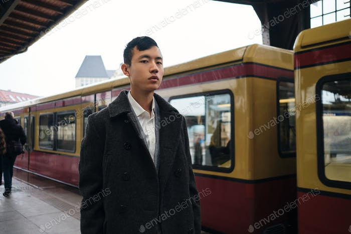 Young stylish Asian businessman confidently looking in camera while waiting train on subway platform