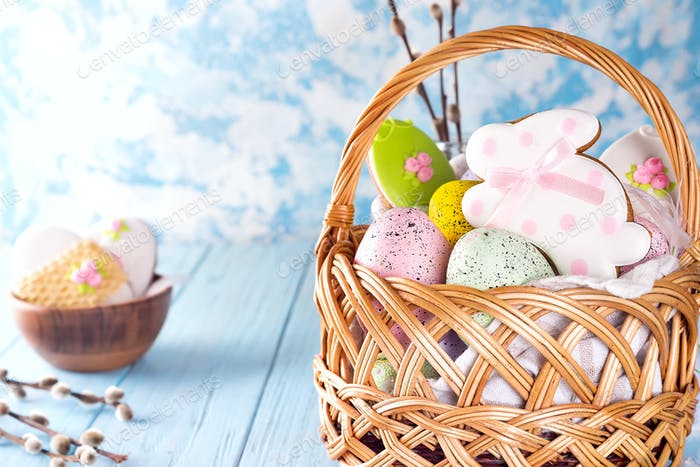 Colorful easter eggs and glazed cookies in basket on blue wooden background