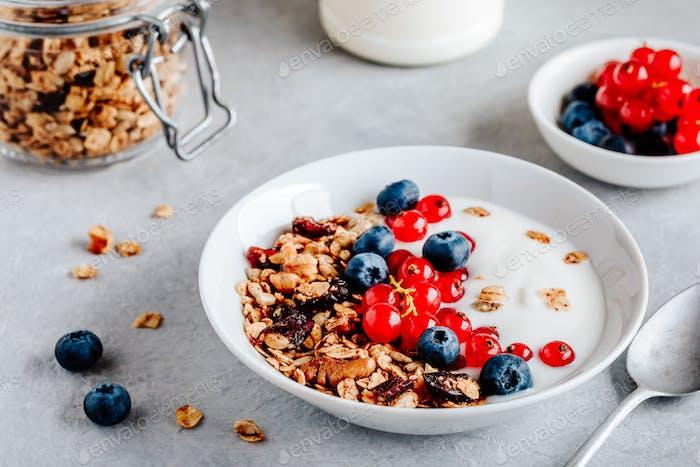Gesunde Frühstückschale mit Müsli, Blaubeeren, roten Johannisbeeren und Joghurt.