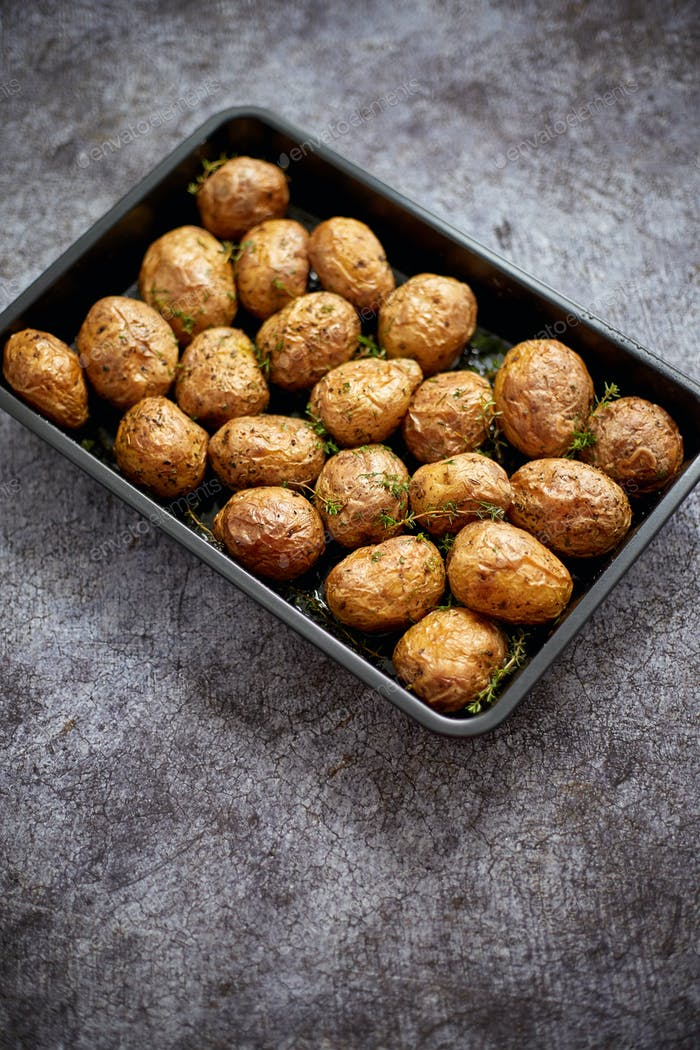 Homemade roasted whole potatoes in jackets. With butter, rosemary and thyme. Served in metallic dish