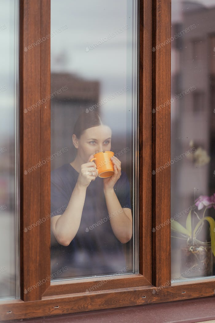 Young woman looking through window at the city while drinking tea