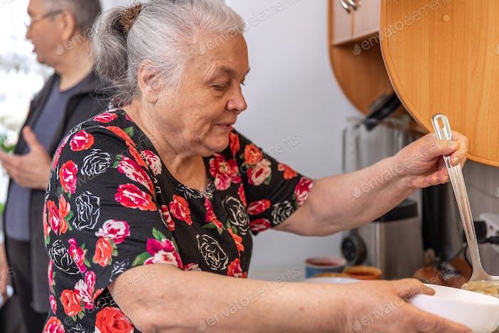 Eine alte Frau am Herd gießt Suppe in einen Teller.