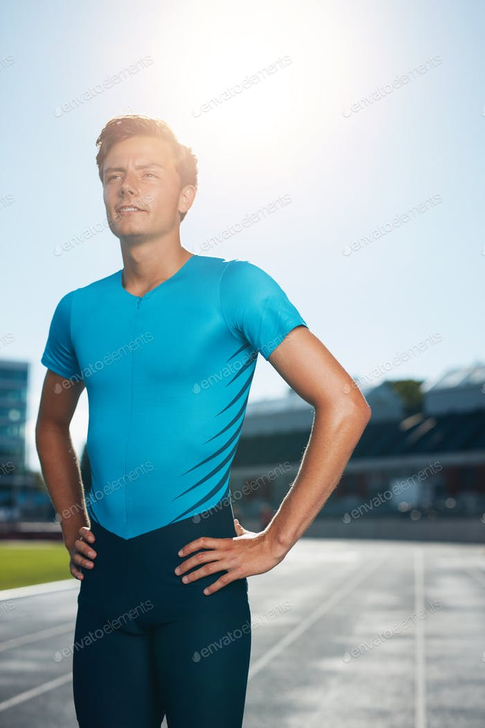 Sprinter stands in athletics stadium