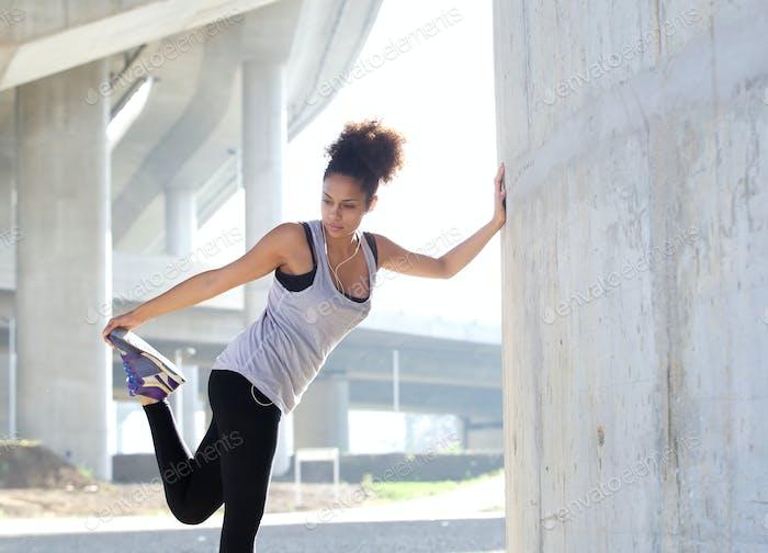 Junge Frau Stretching Beinmuskulatur im Freien