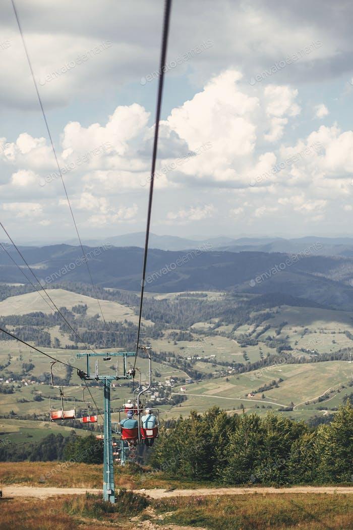 Alte Sesselbahn mit Menschen in den Karpaten am sonnigen Tag