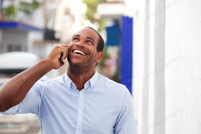 cheerful man standing outside on street talking on mobile phone