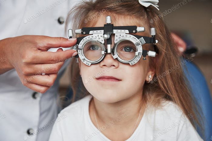 Health care of the eyes. Doctor checking little girl sight and tuning the phoropter