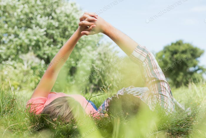 Cute couple holding hands in the park on a sunny day
