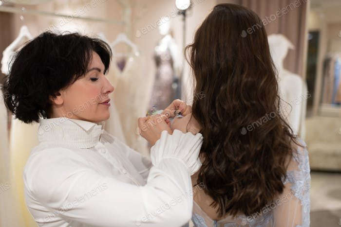 Wedding designer and female client trying on dress