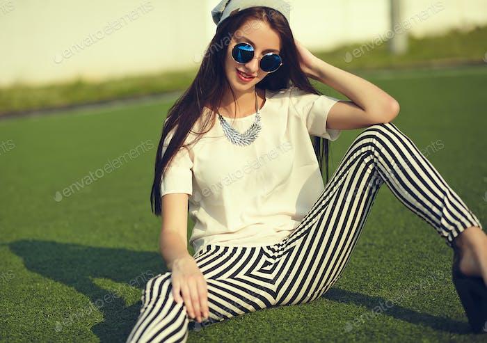 Porträt einer jungen stilvollen Frau, die auf dem Rasen sitzt