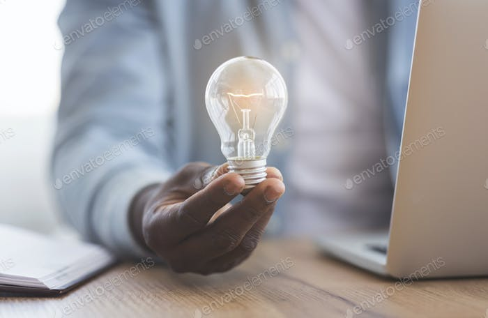 Black businessman holding illuminated light bulb in hand