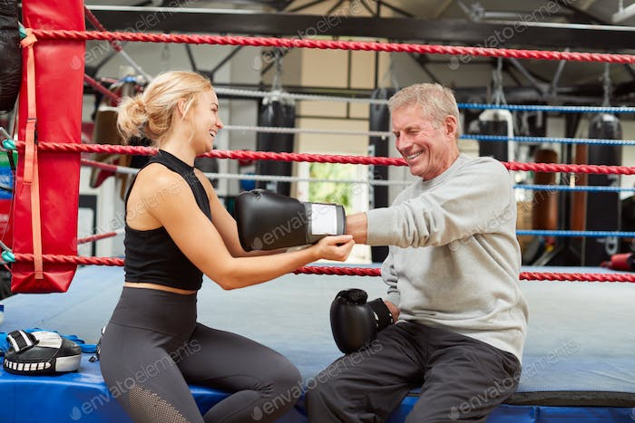 Personal Trainer Helping Senior Male Boxer In Gym To Put On Boxing Gloves In Gym