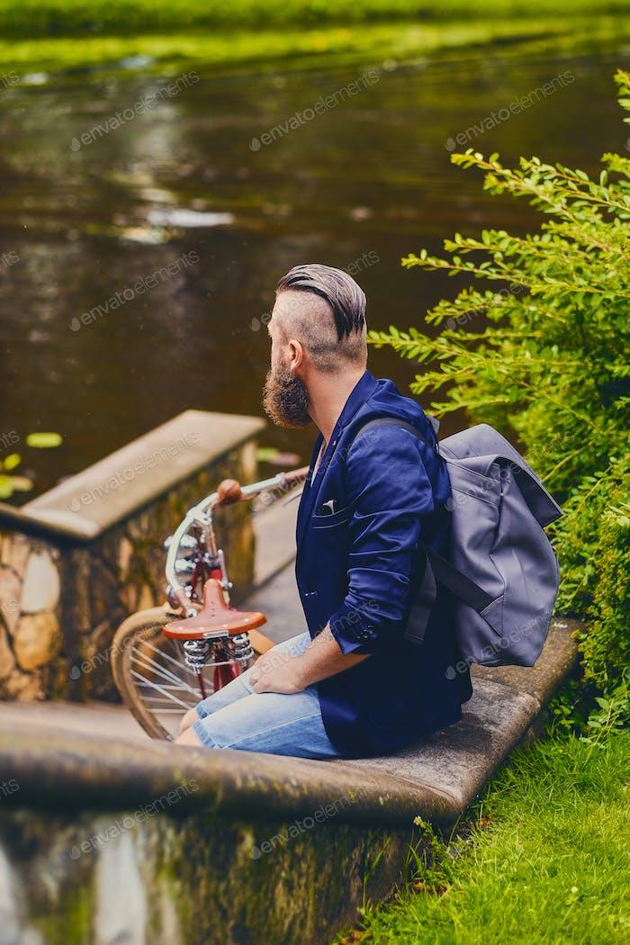 Человек на ретро-велосипеде в парке.