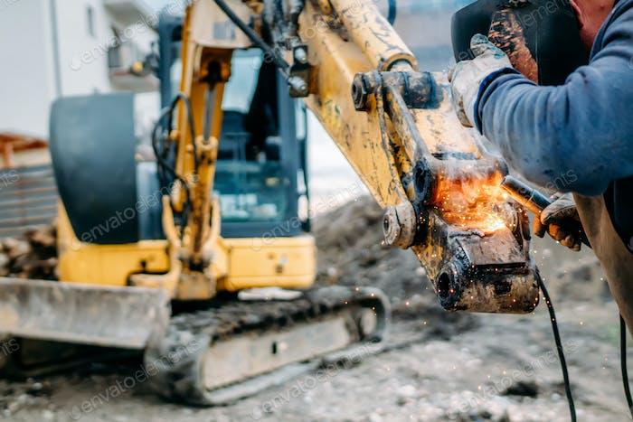 Professional worker welding excavator arm on construction site