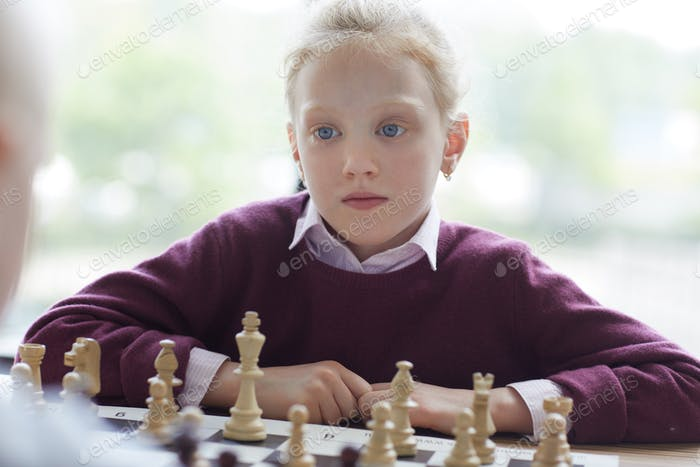 Blue-eyed girl playing chess