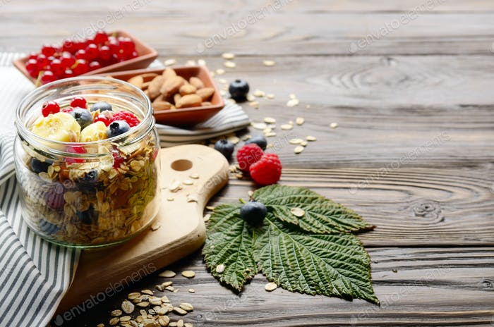 Fruit healthy muesli in glass jar on kitchen wooden table