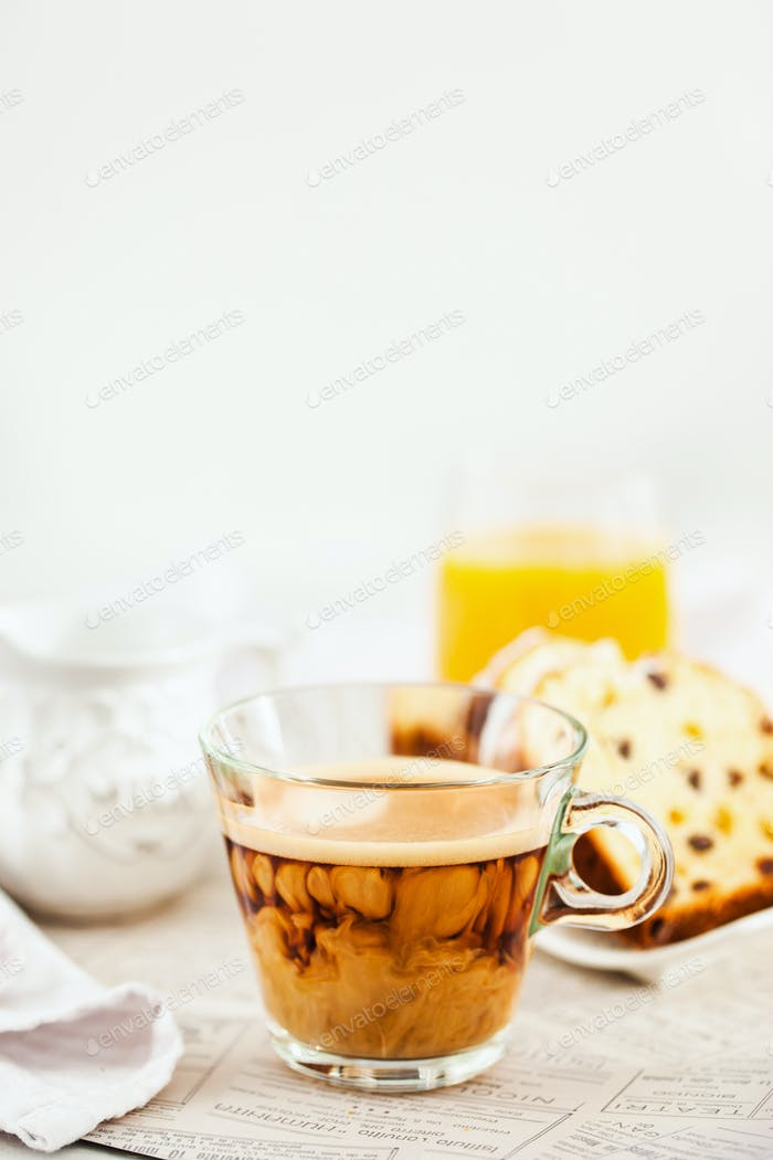 Continental breakfast table with cup of hot  coffee with milk, c