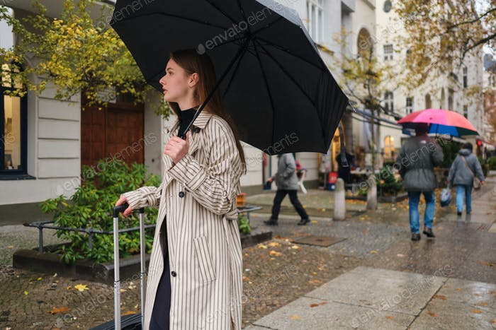 Beautiful stylish girl walking around rainy street with umbrella and suitcase