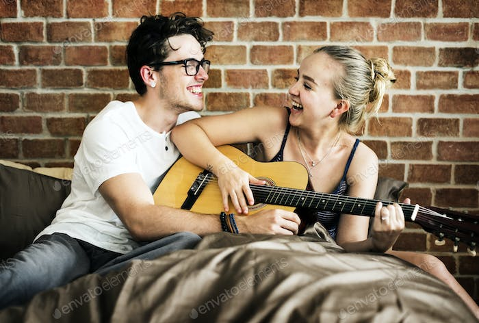 Caucasian couple playing guitar together