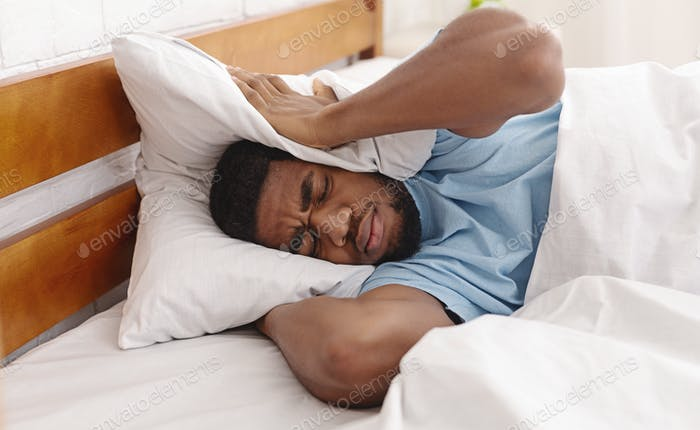 Young man in bed hiding under pillow