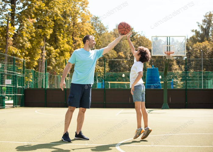 Mature man teaching boy how to play basketball