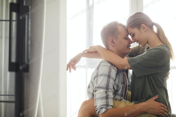 Young amorous couple looking at one another while embracing
