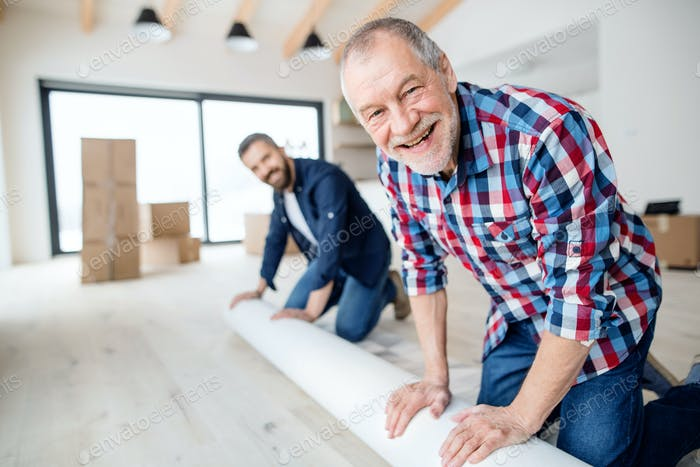 A senior man helping his son with furnishing new house, a new home concept.