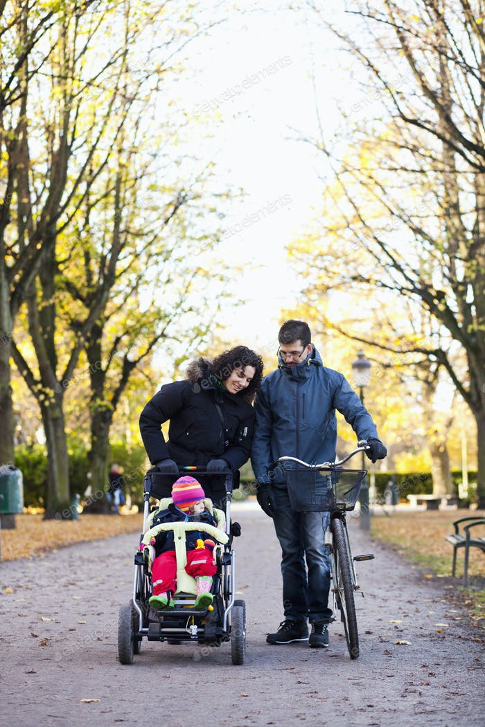 Parents looking at girl on baby carriage in park