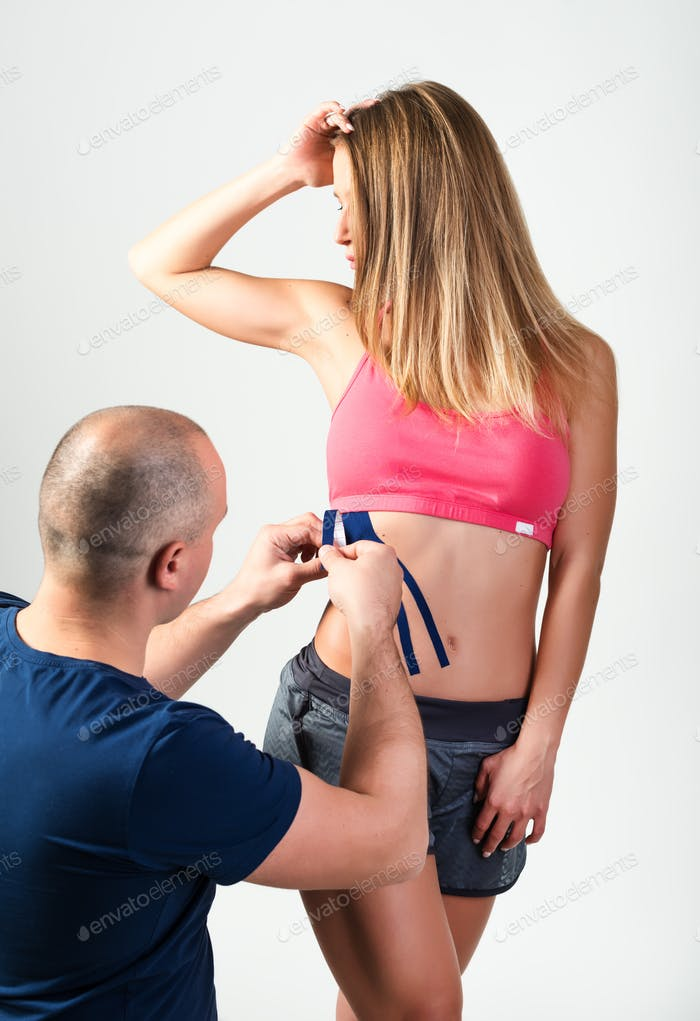 The therapist glues therapeutic tapes on the woman stomach