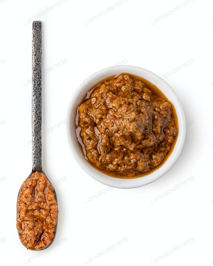 Bowl and spoon with red pesto sauce