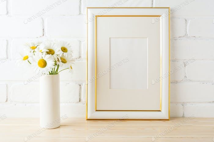 Gold decorated frame mockup with daisy near painted brick wall