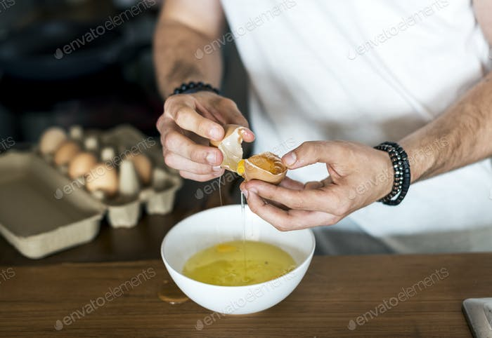 Closeup of man separating egg yolk
