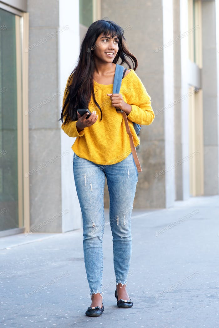 Full body young Indian woman walking with cellphone in the city