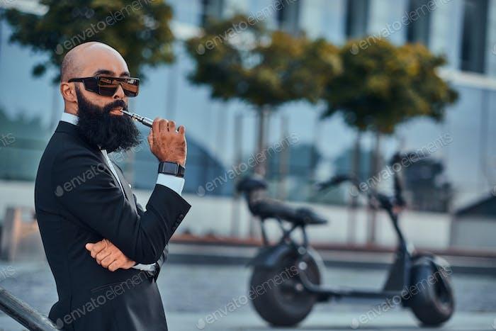 Современный бородатый мужчина курит варизер