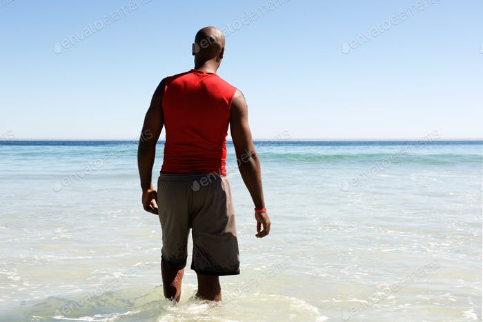 African man walking in to the sea water