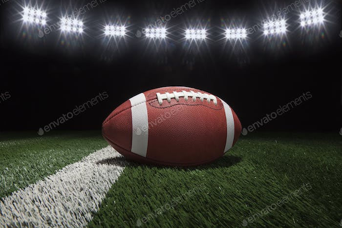 College Football on Field with Dark Background and Lights