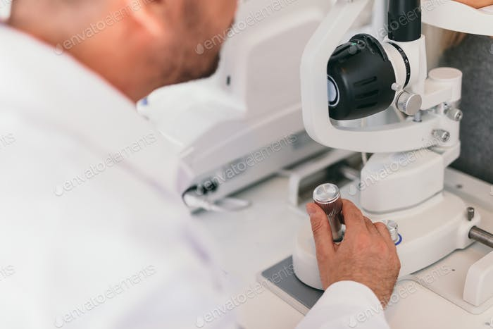Doctor operating an optical machine.