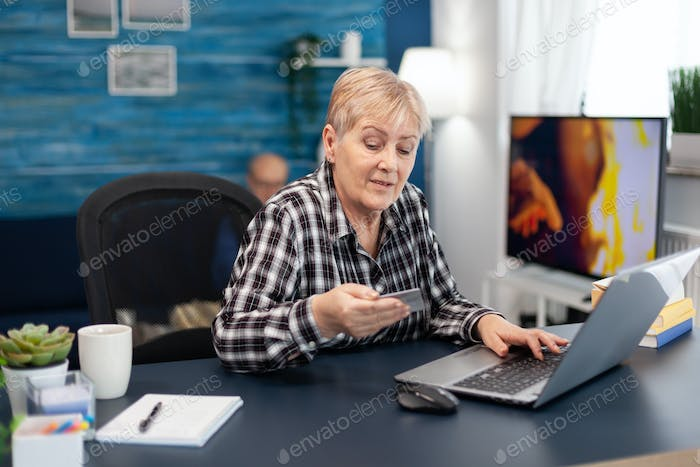 Senior woman reading cvv code from credit card