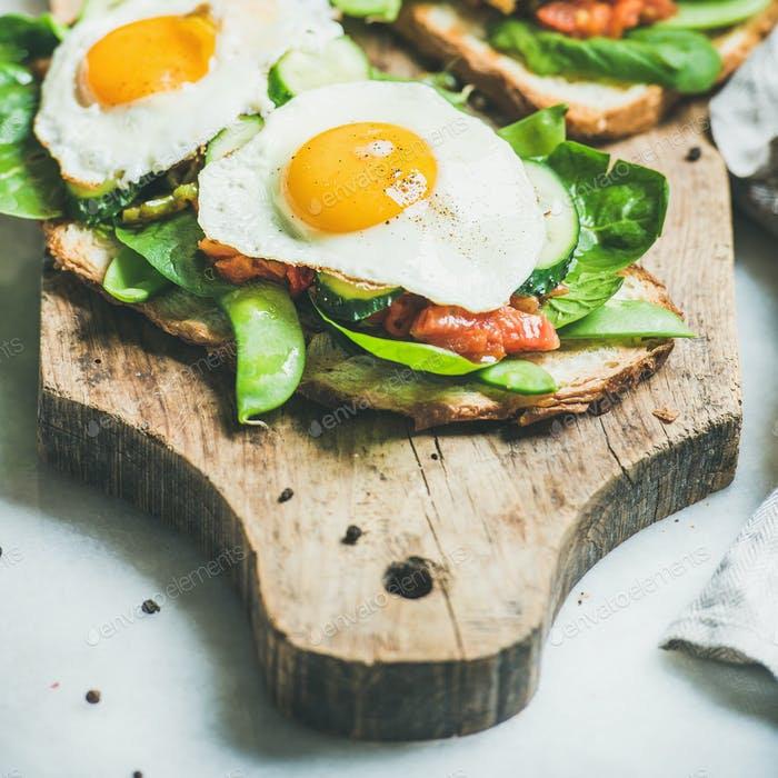 Bread toasts with fried eggs and fresh vegetables, square crop