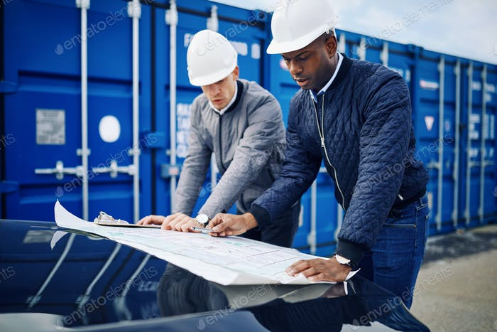 Two engineers discussing building plans together in a container yard