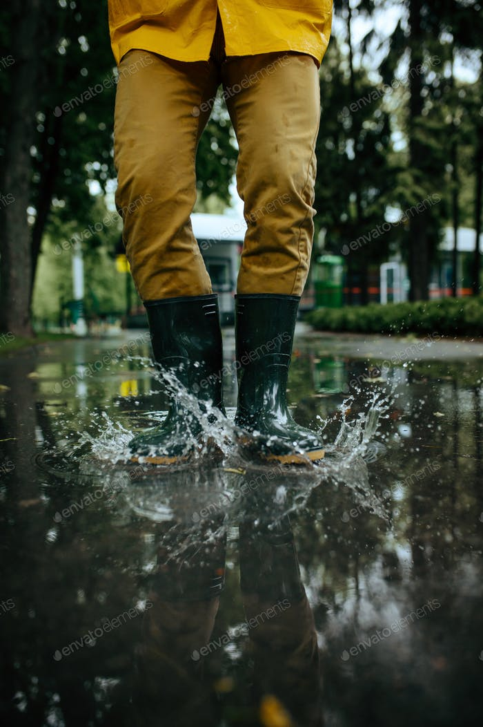 Male person in rubber boots jumping in puddles