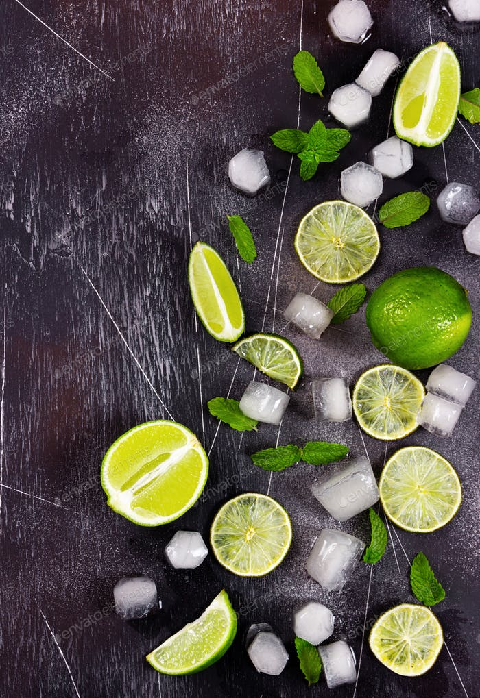 Fresh lime, mint and ice on dark background.