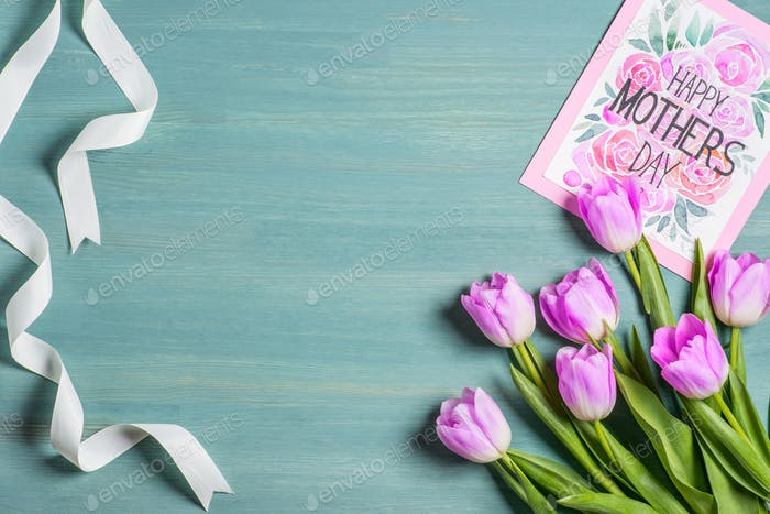 top view of white ribbon, bouquet of tulips and card with lettering happy mothers day on blue