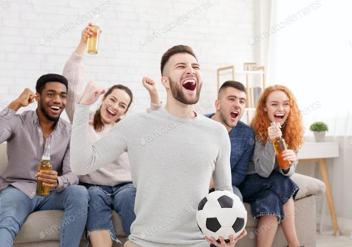 Happy football fans watching match on tv