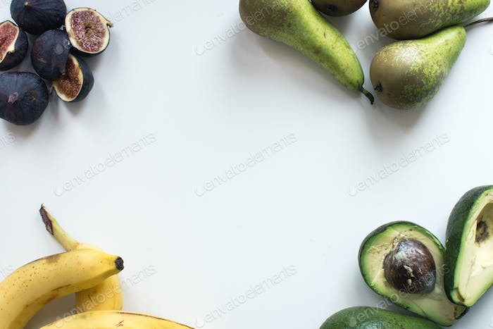 Aerial shot of fresh figs, bananas, pears and avocados on a white background