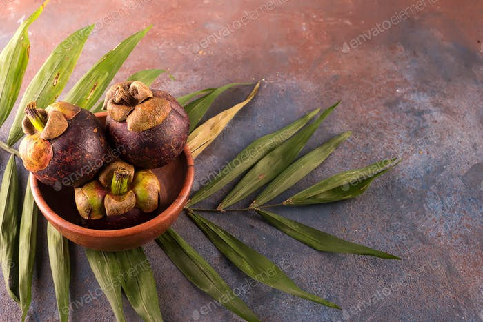 Mangosteen fruit on bamboo bowl on stone background
