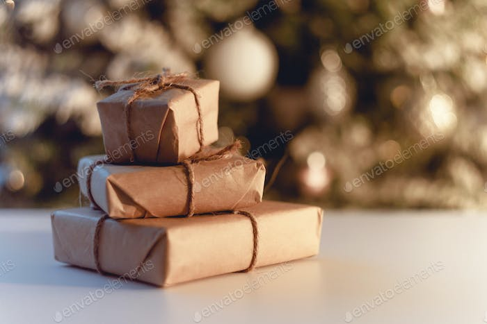Stacks of Christmas presents with decorated Christmas tree in background