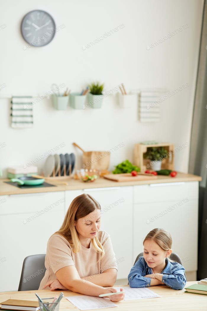 Adult Mother Helping Daughter Studying at Home