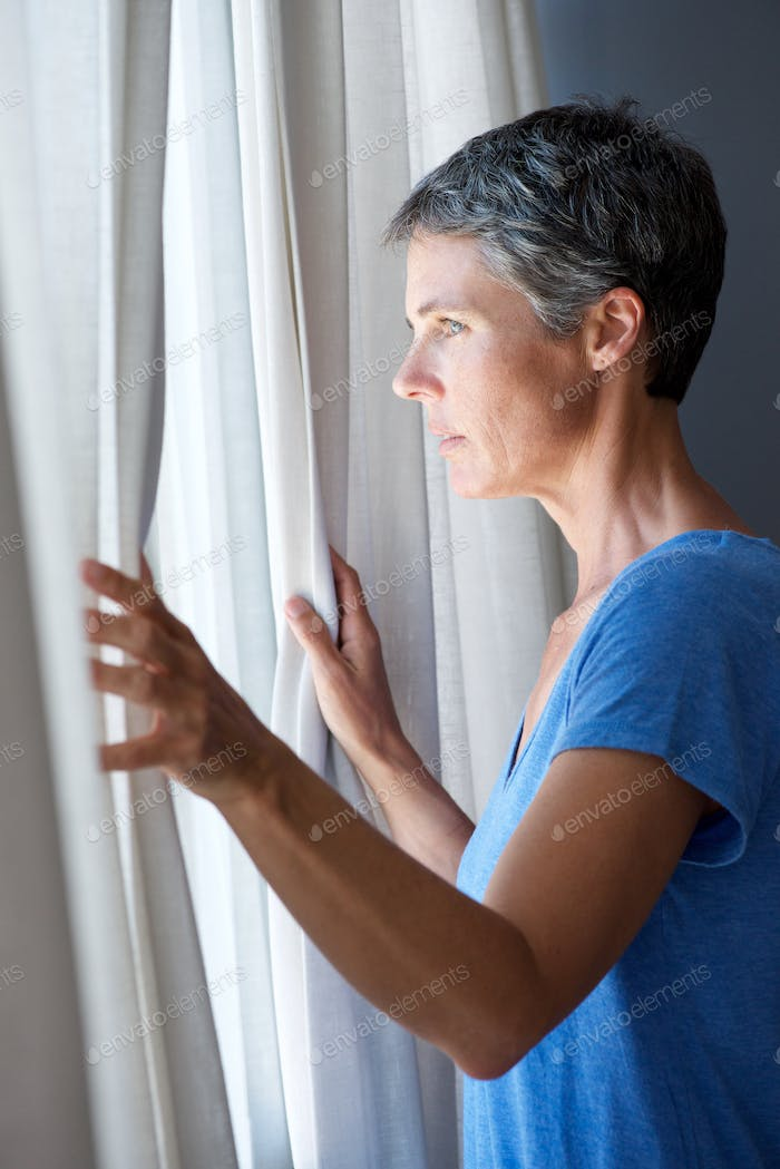 older woman opening curtains and looking out window