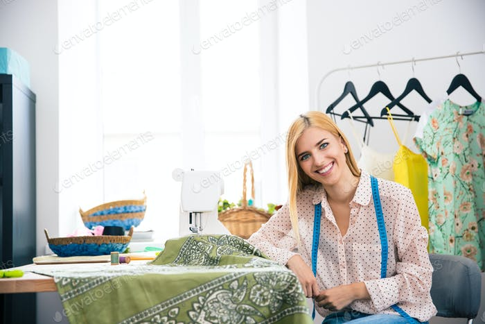 Happy female tailor sitting at her workplace